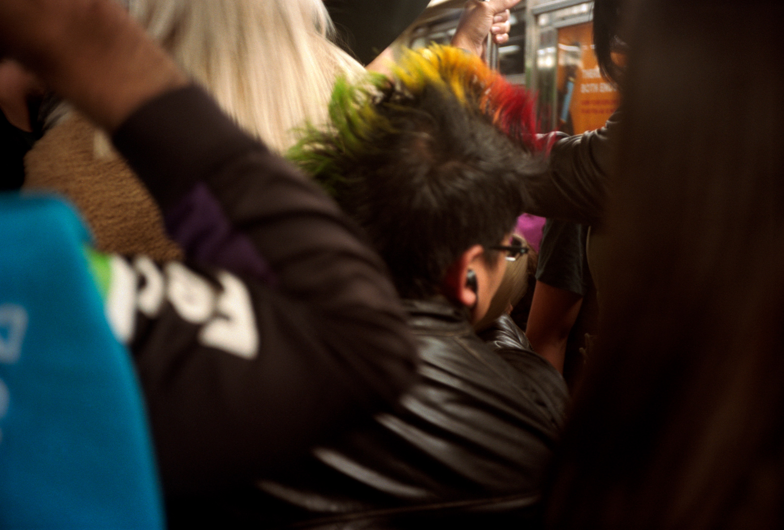 Stuck on the New York Subway, Woman with rainbow coloured mohican hair, Lonely New York Photography Ioannis Koussertari.