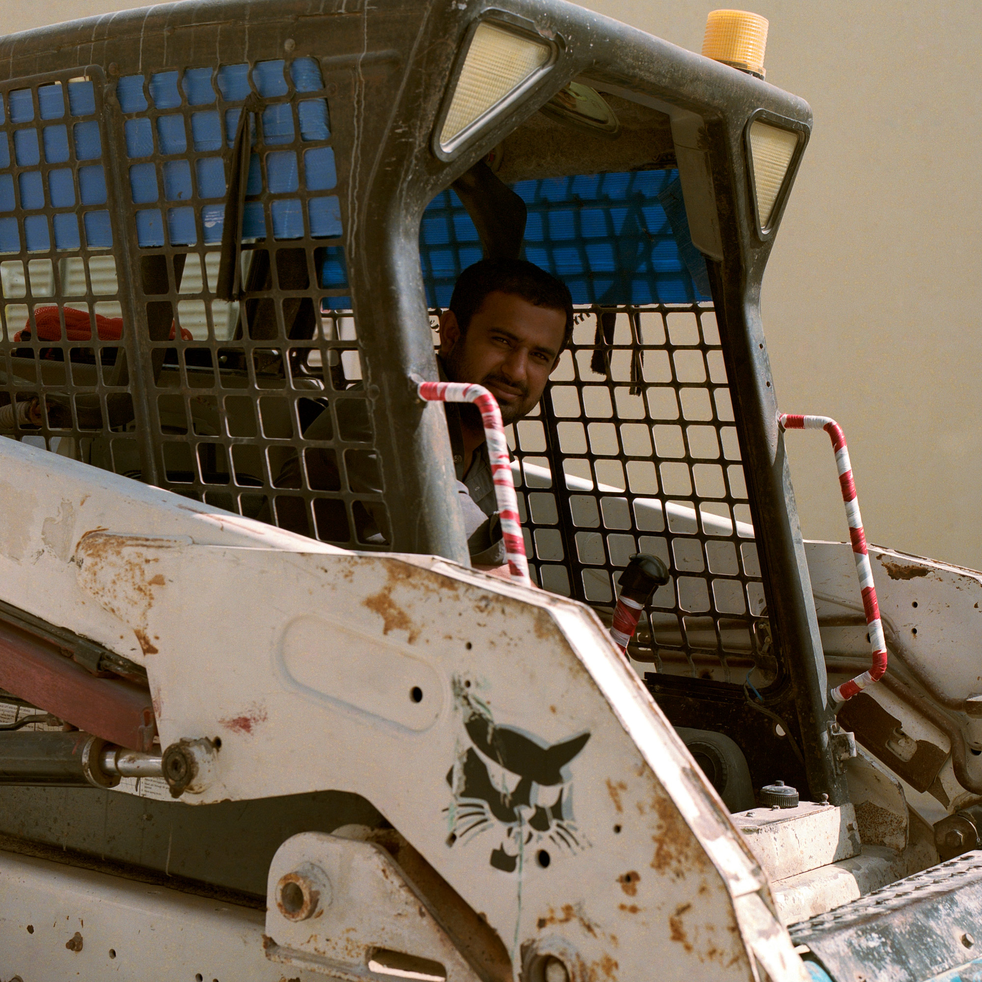Indian construction worker at work with digger, on worksite. Dubai Labourers.
