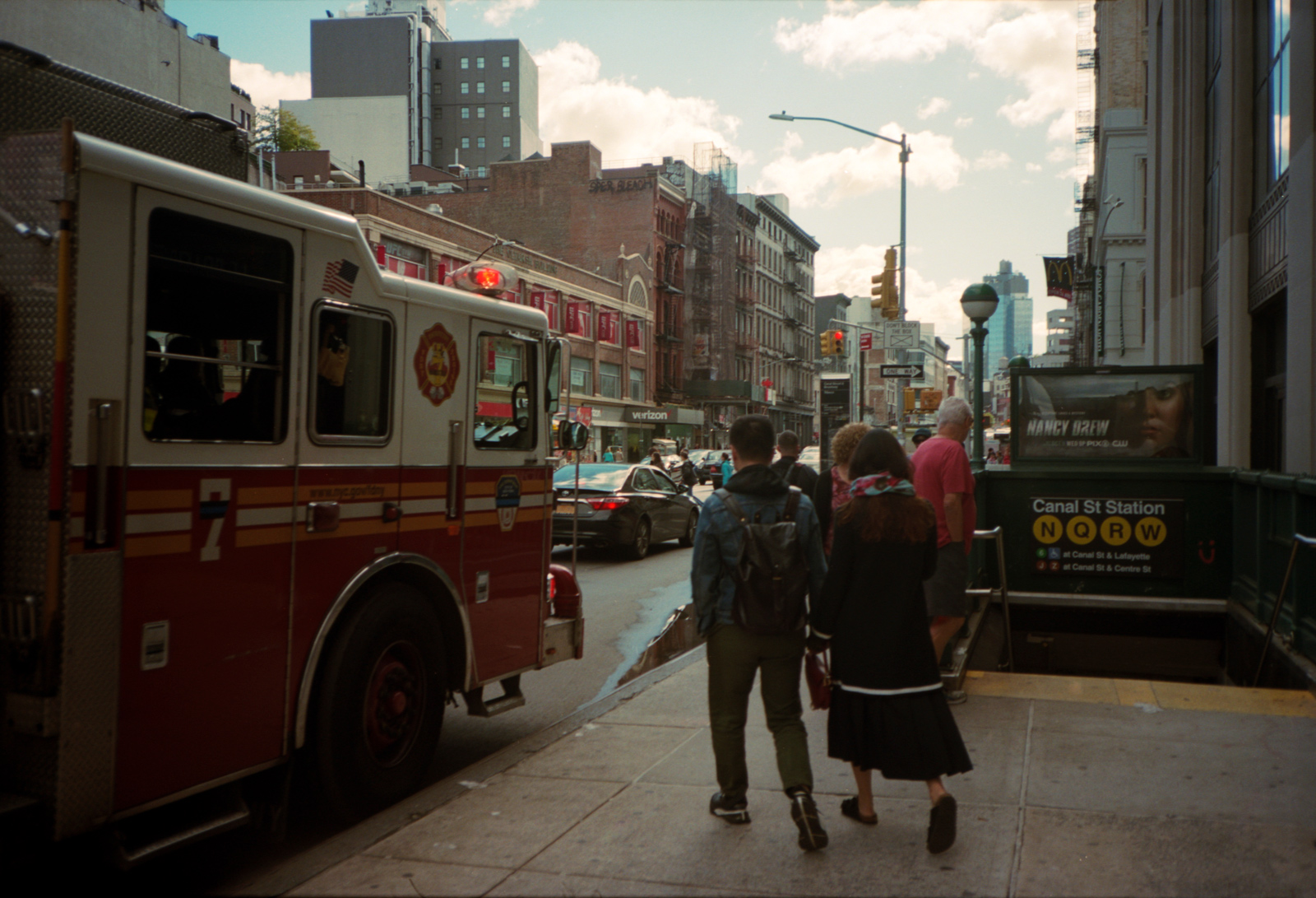 A fireman taking a picture from the fire truck of people passing Canal St Station Subway. Lonely New York Series. Photography By Ioannis Koussertari.