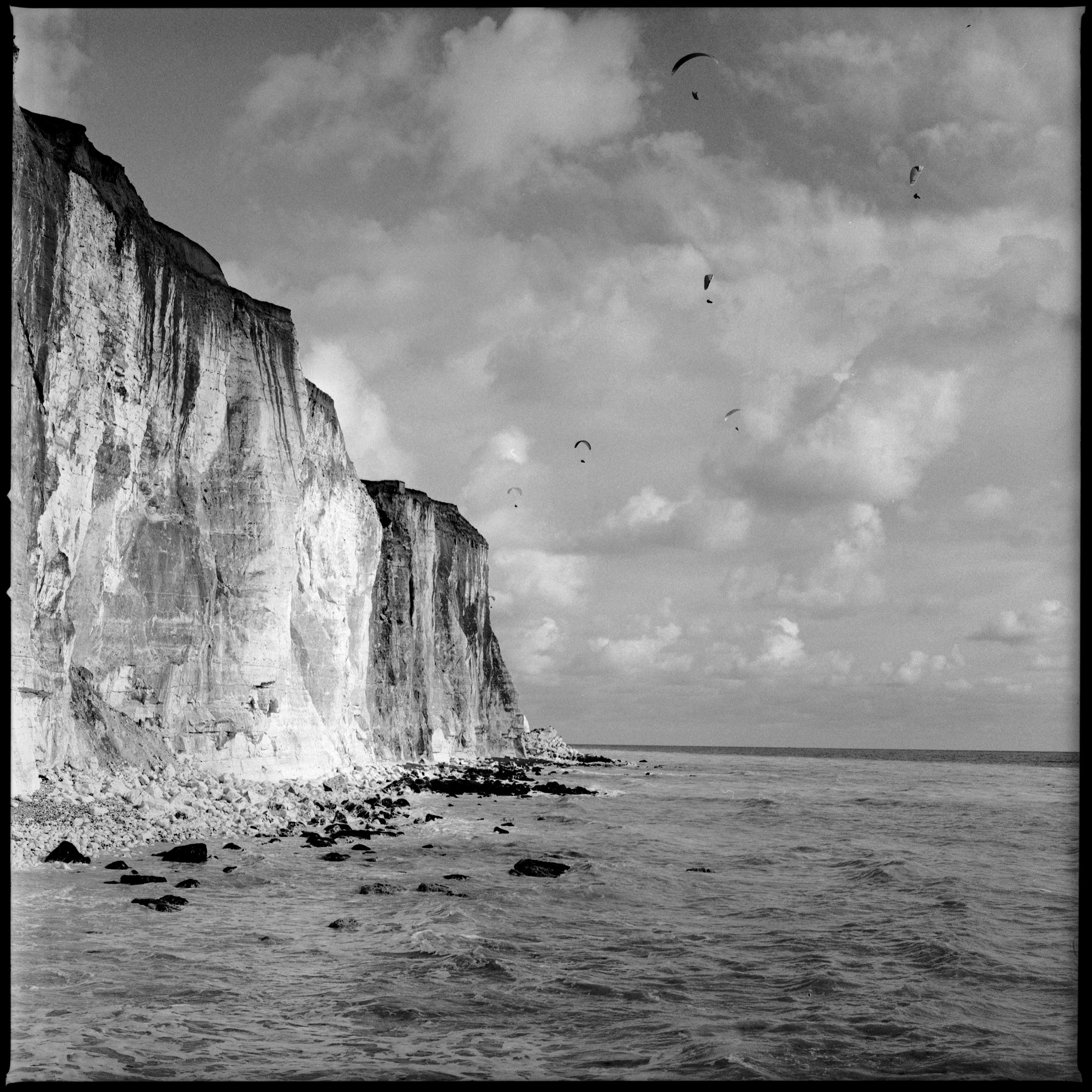 Paragliders Peacehaven cliff edge, black and white photo on film by ioannis koussertari.