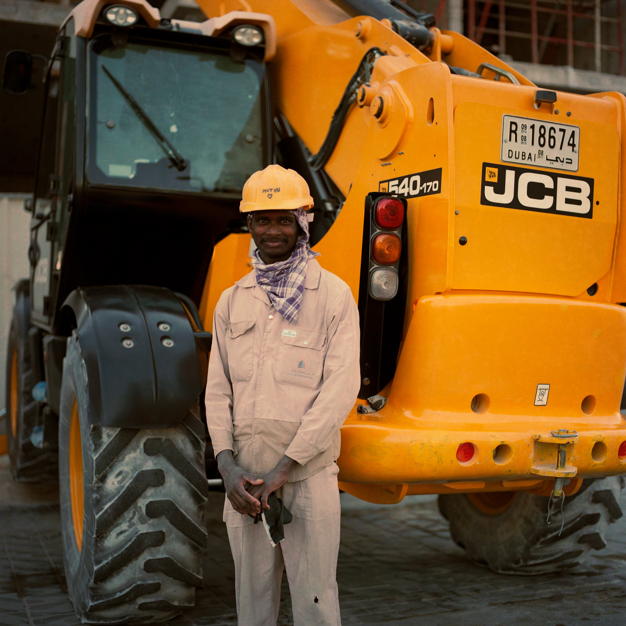 Indian construction worker, in front of digger. Dubai Labourers.
