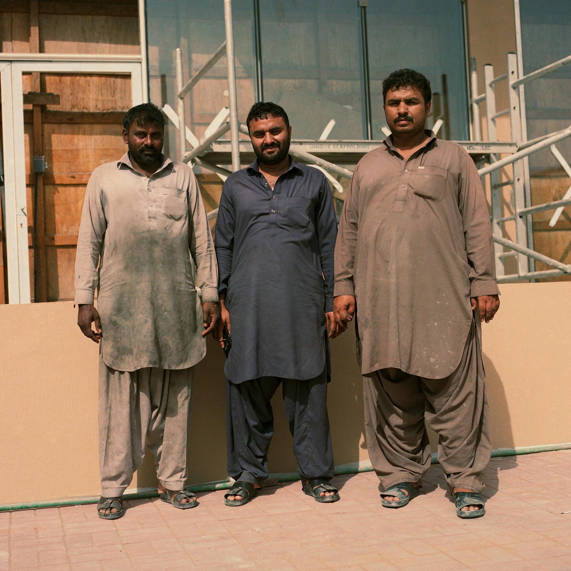 Dirty Clothes, three Indian construction workers in front of construction site in traditional workwear. Dubai Labourers.