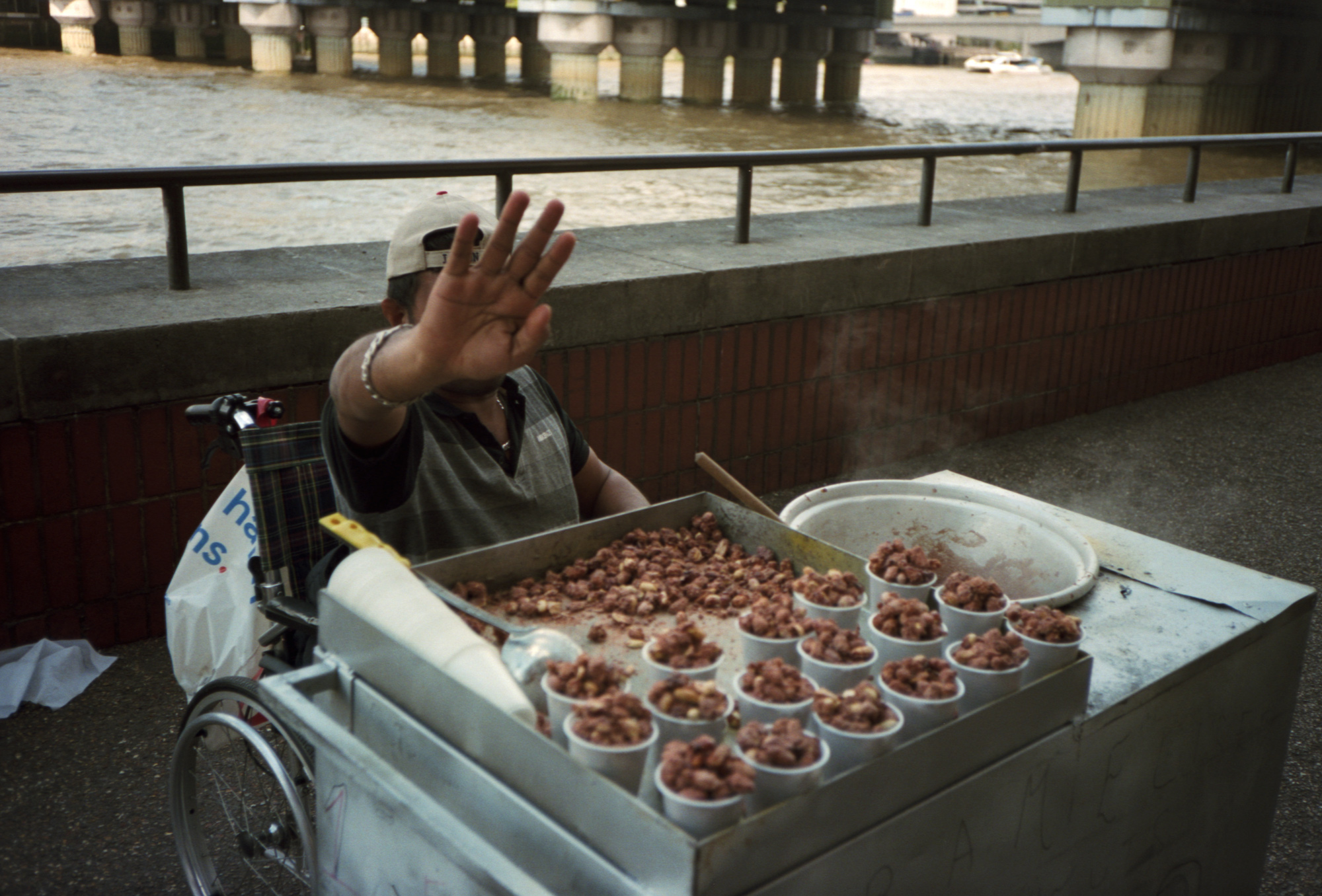 Man selling peanuts on the river thames in London, Observations Series, Photography By Ioannis Koussertari 2020