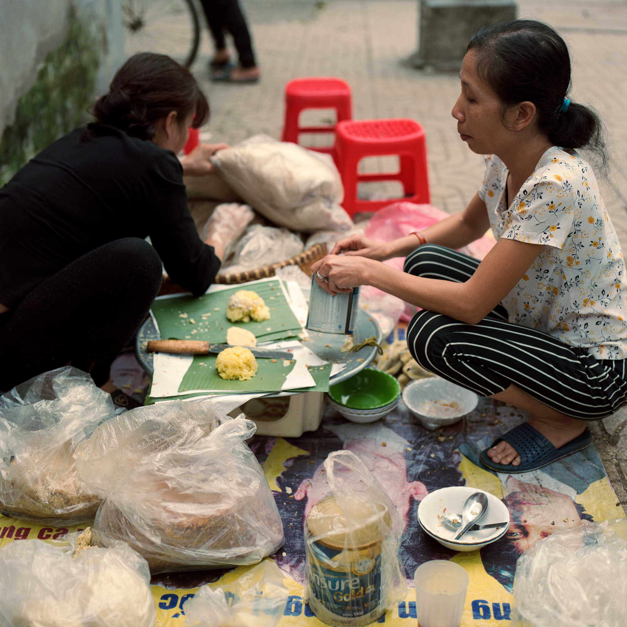 Woman vendors making breakfast at the side of the road in Hanoi Vietnam. Eastern Travels, Photography By Ioannis Koussertari
