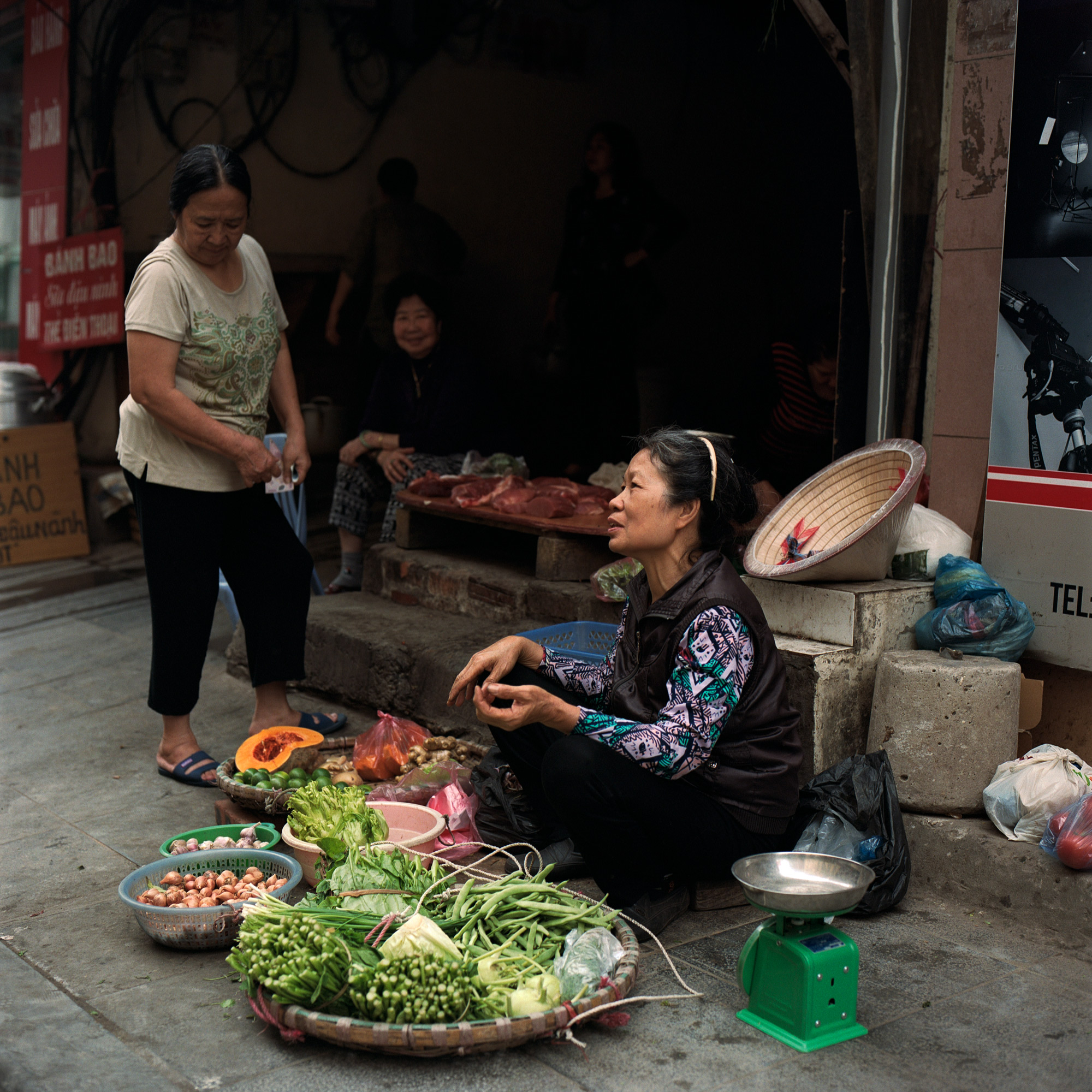 Woman vendor with baskets of fresh fruit and veg, at the side of the road in Hanoi Vietnam. Eastern Travels, Photography By Ioannis Koussertari
