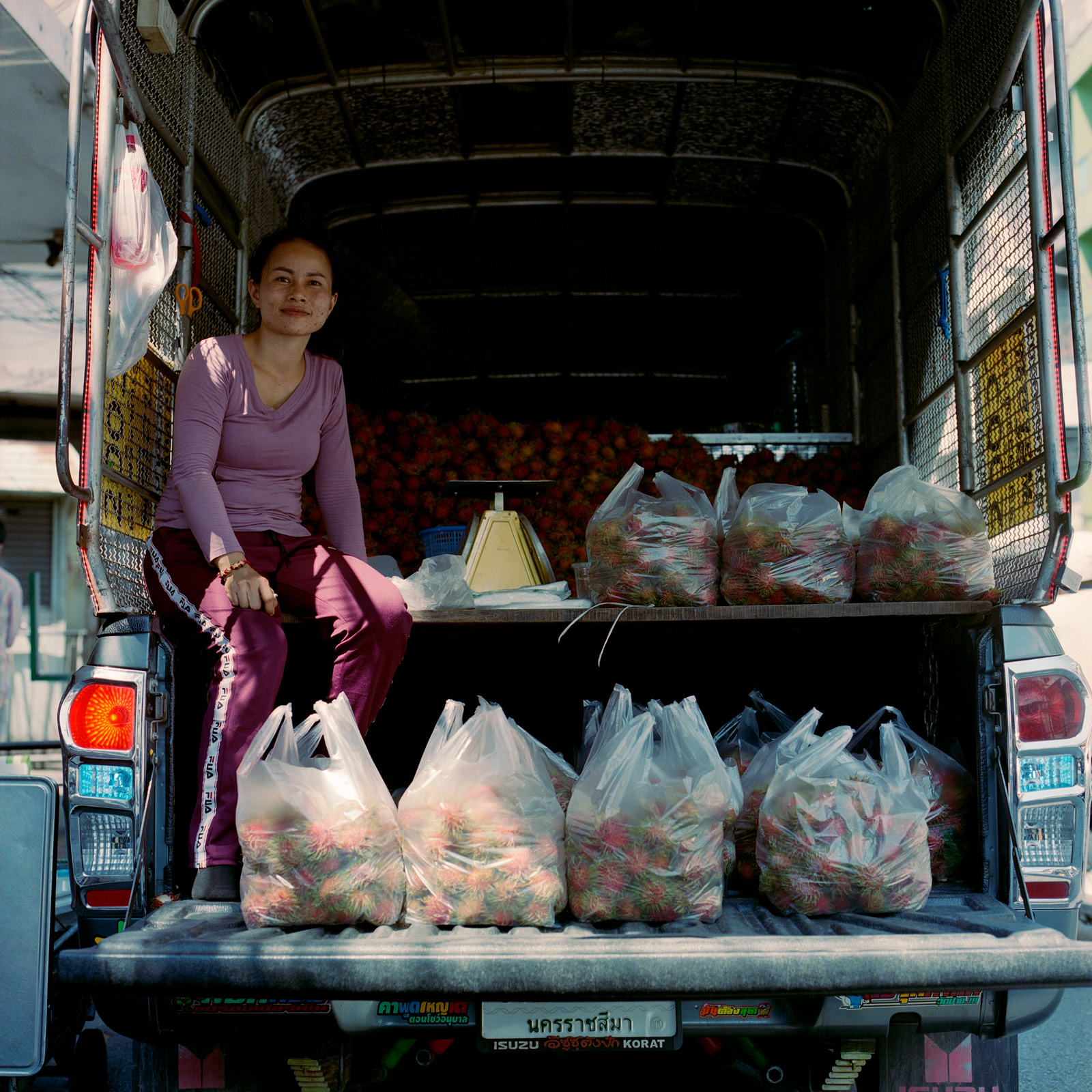 street market seller, girl, on back of truck, selling bags of rambutan fruit, off Mittraphan Road, Bangkok, Eastern Travels, Photography by Ioannis Koussertari