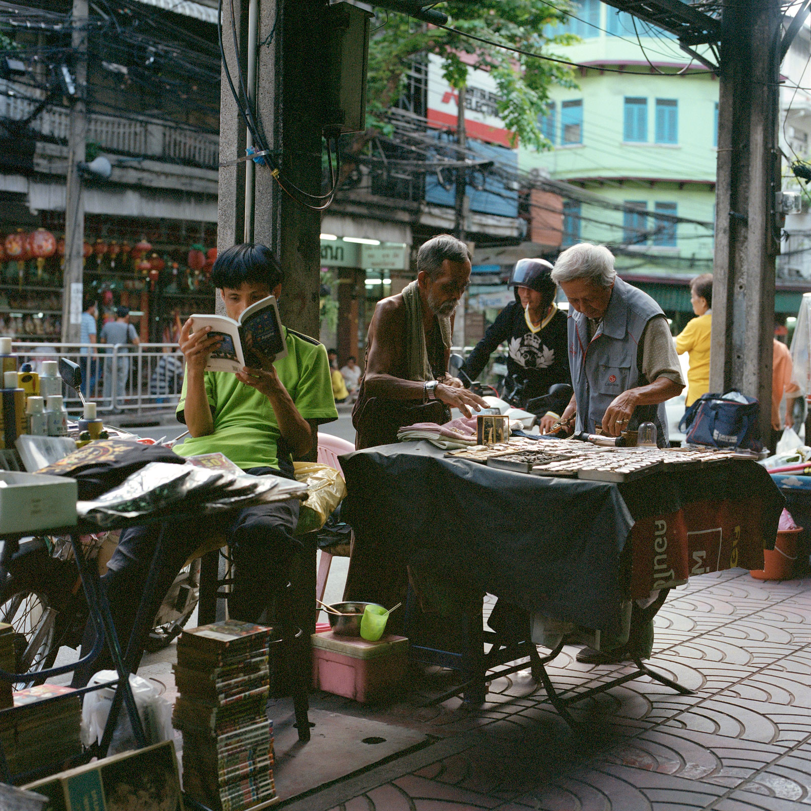 a man reading a book, amongst street traders off Yaowarat Road, Chinatown, Bangkok Thailand. Eastern Travels, Photography By Ioannis Koussertari