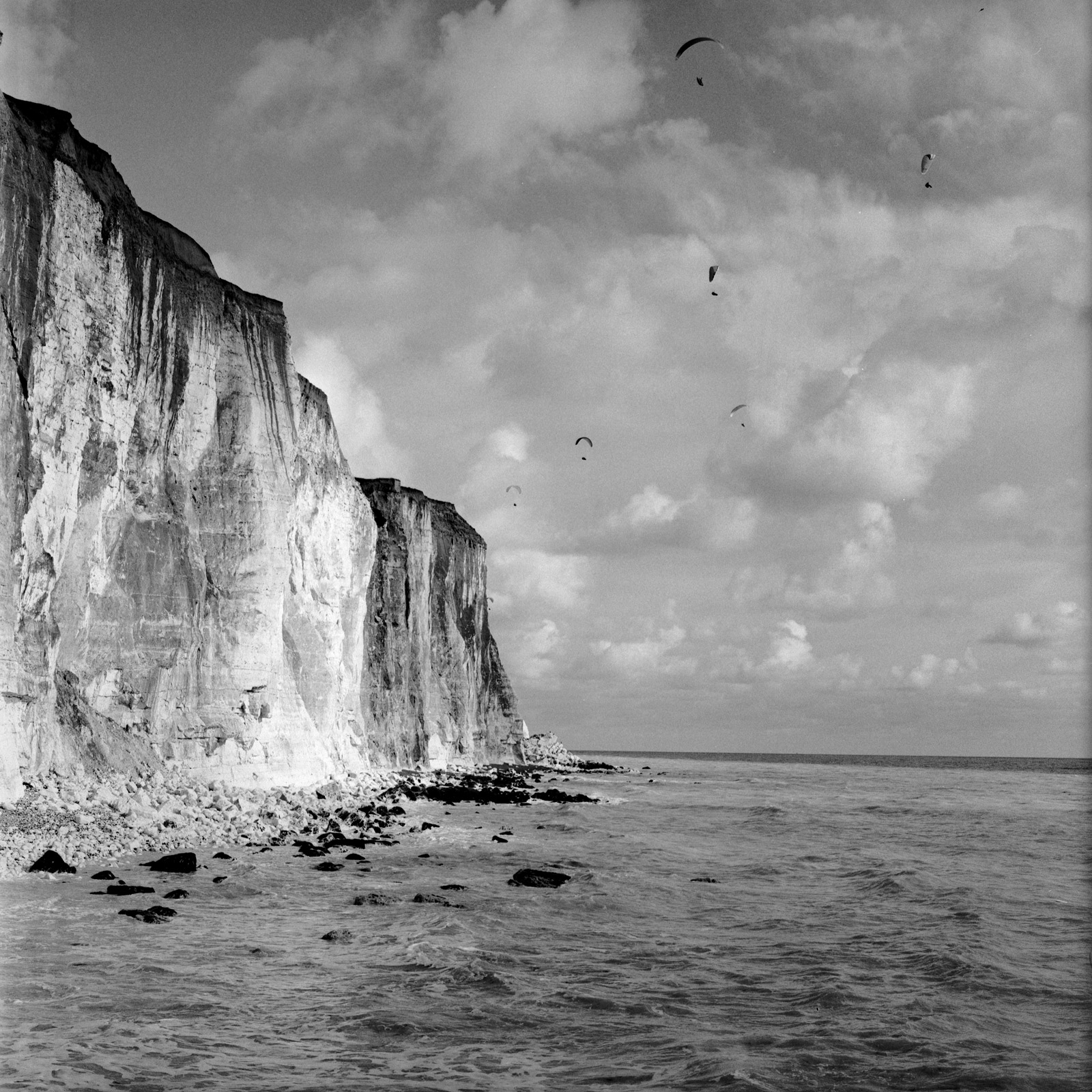Paragliders, Image was photographed in the South East of England. Situated on the Peacehaven Promenade walk in 2020. Part of a wider Observations series. Using a Hasselblad 6x6 camera and Ilford FP4 125iso film, hand developed in Ilfosol 3 chemicals in 2020. Black & White archival print using traditional darkroom chemical process. Black & White archival print using traditional darkroom chemical process. Using Ilford Multigrade RC Deluxe satin paper. 10x8in print (20.3cm x 25.4cm) Medium weight 190 Limited edition print £100 GBP