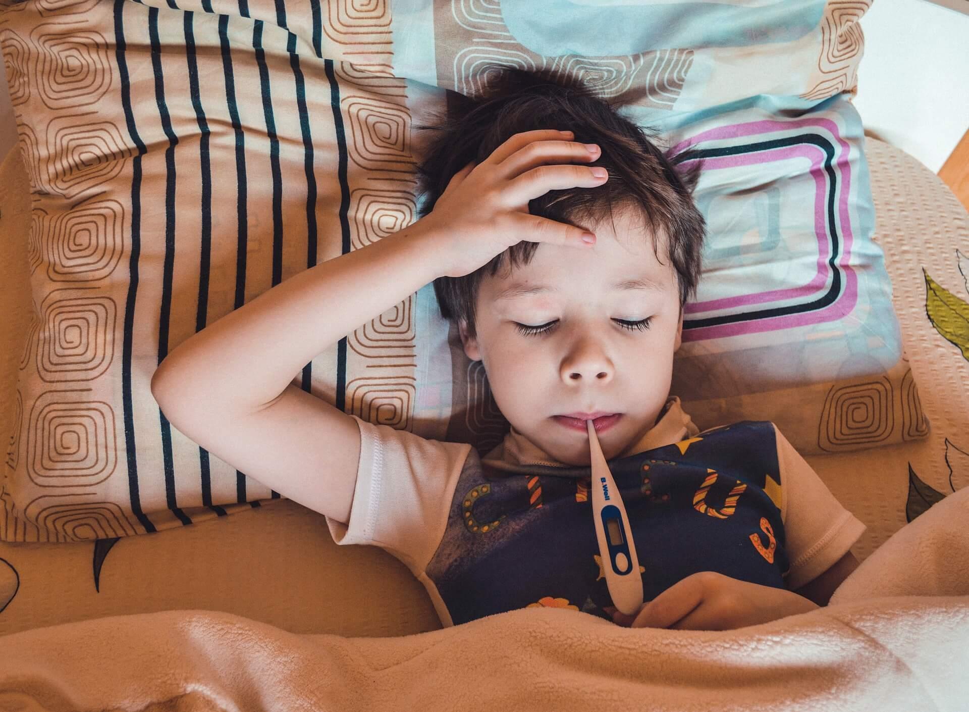 Bolestan dječak u krevetu s toplomjerom u ustima