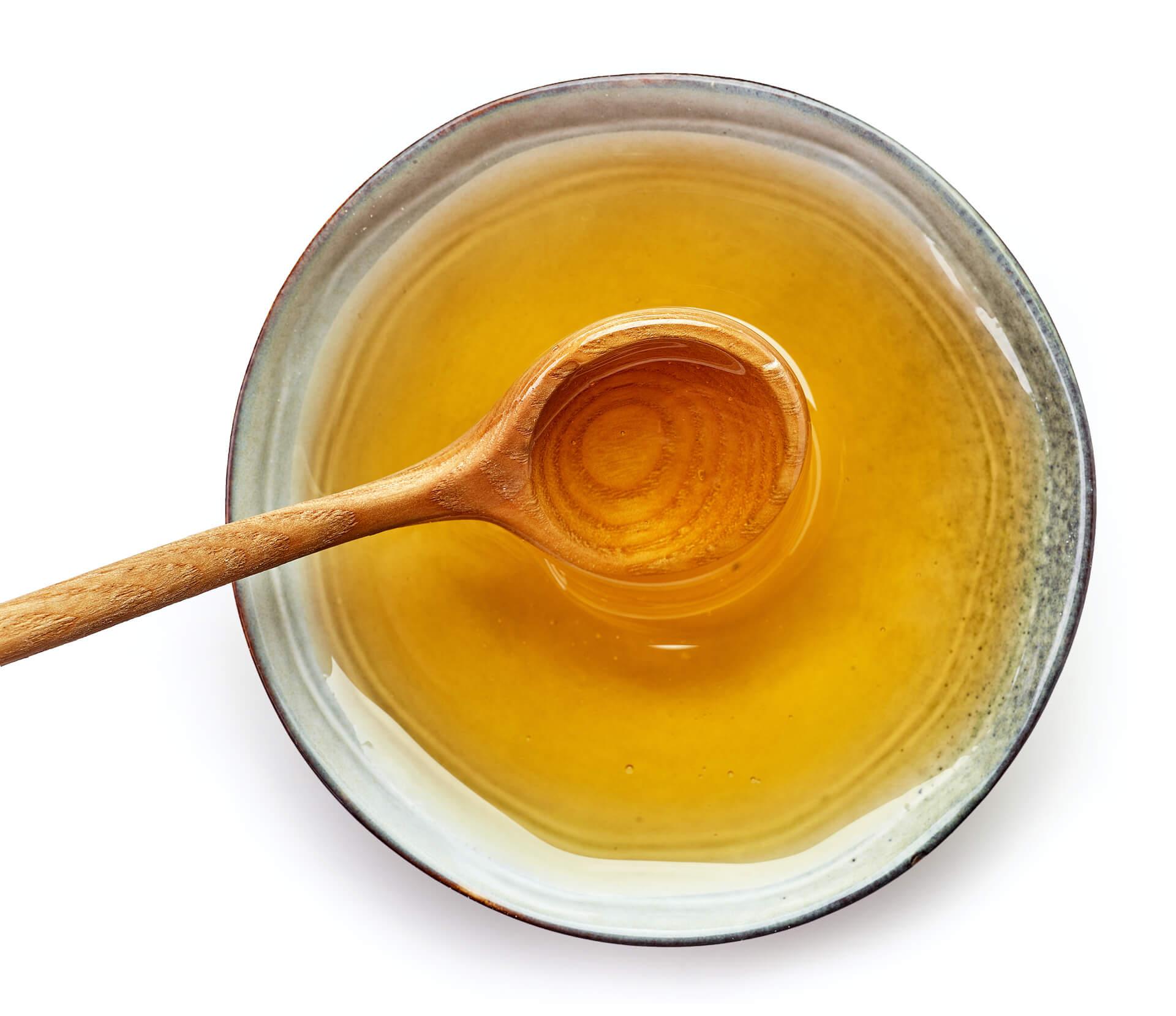 Med u keramičkoj posudi s drvenom žlicom