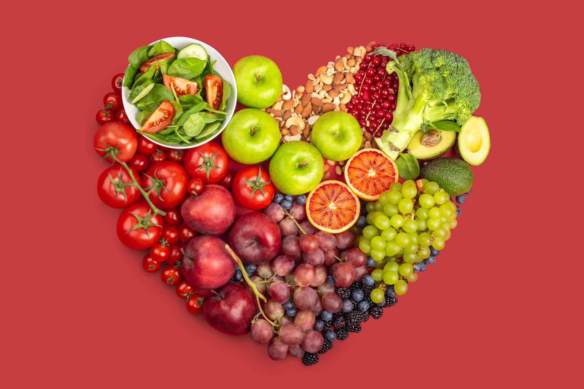 Voće, povrće i orašasti plodovi posloženi u obliku srca na crvenoj podlozi