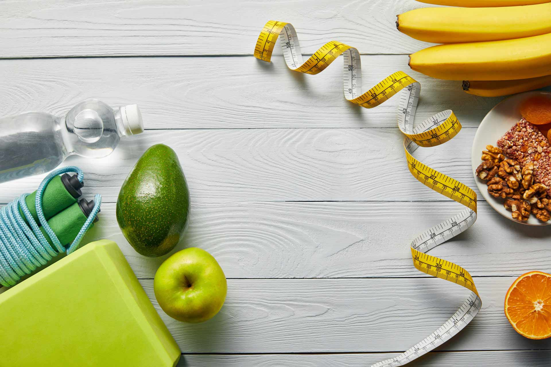Voda , voće, orašasti plodovi i metar za mjerenje opsega tijela na drvenoj podlozi