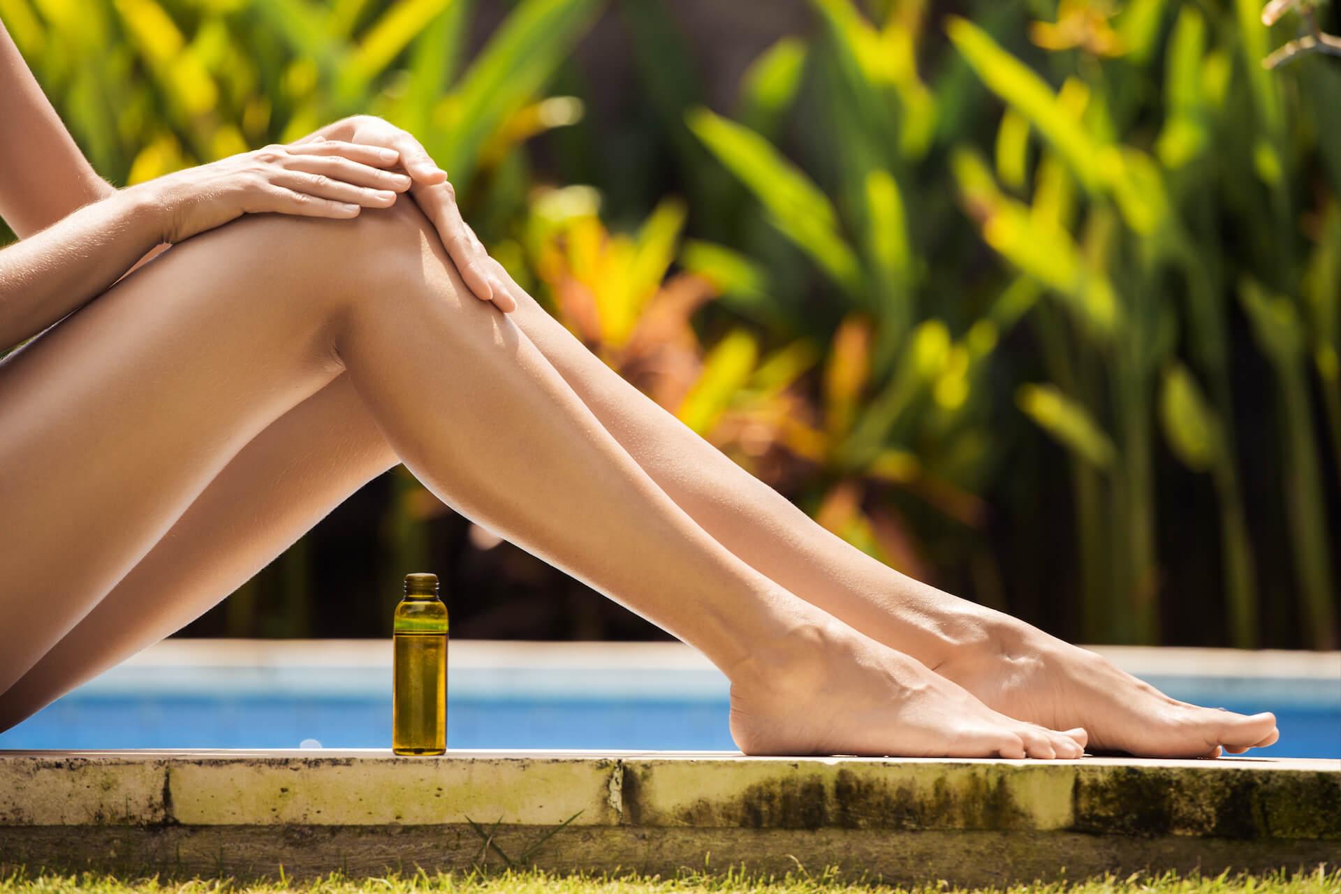Žena na otvorenom nanosi ulje na noge