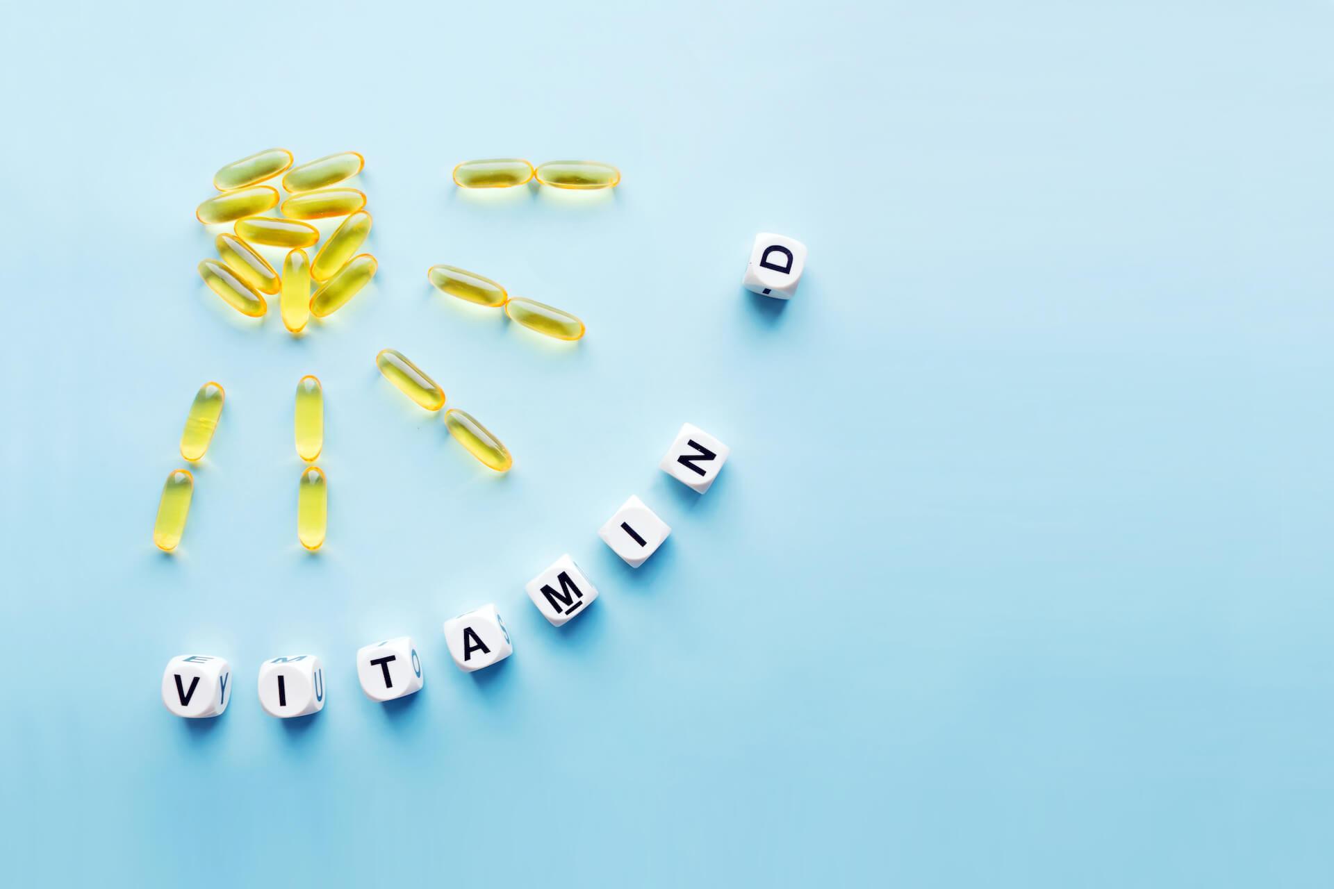 Žute kapsule poslagane u obliku sunca i kockice kojima je ispisano vitamin D