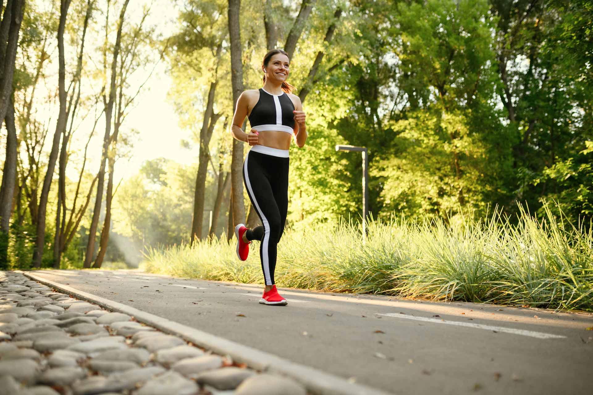 Mlada nasmijana žena u sportskoj odjeći trči u prirodi
