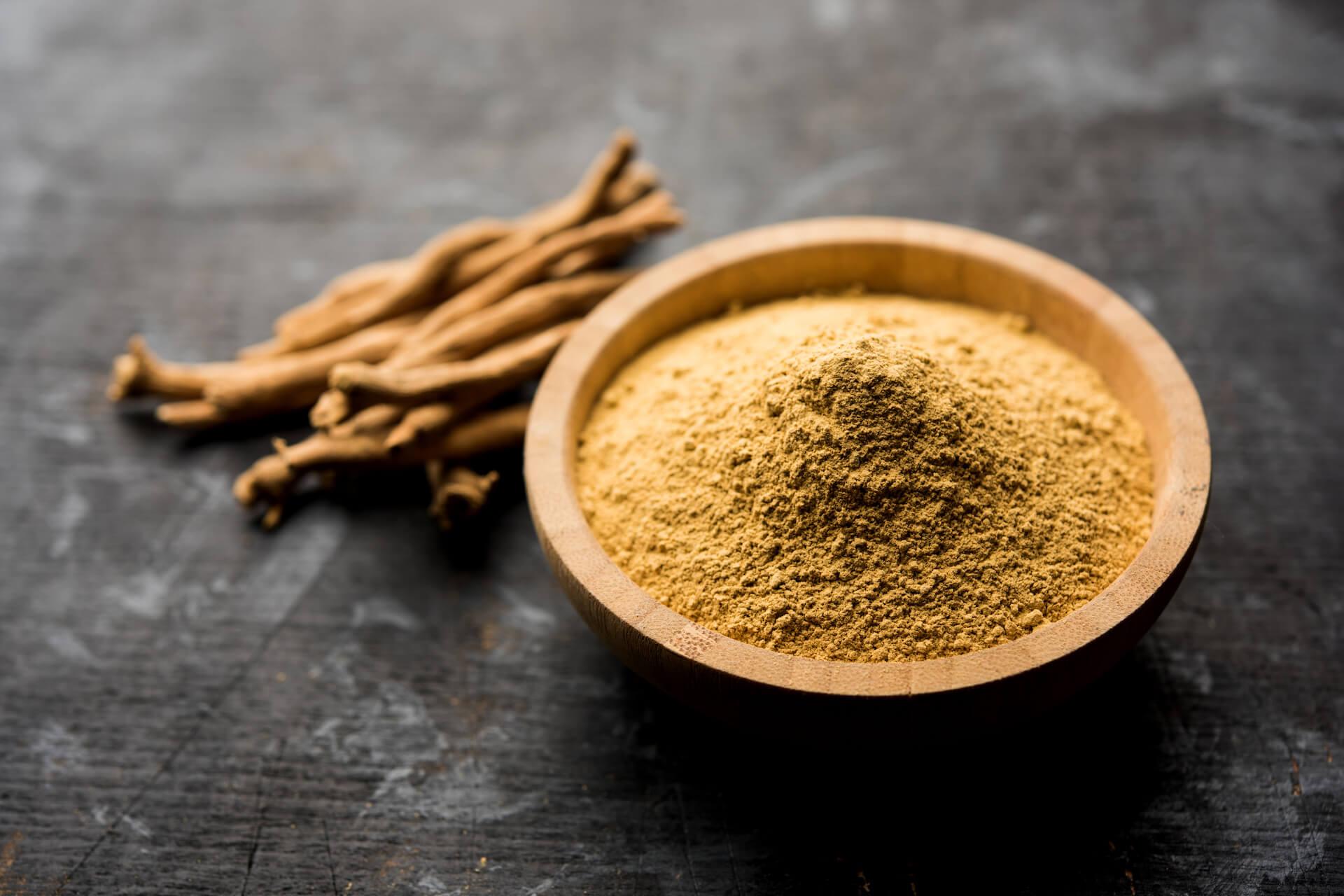 Mljevena ashwaganda u drvenoj zdjelici i suha ashwaganda pored