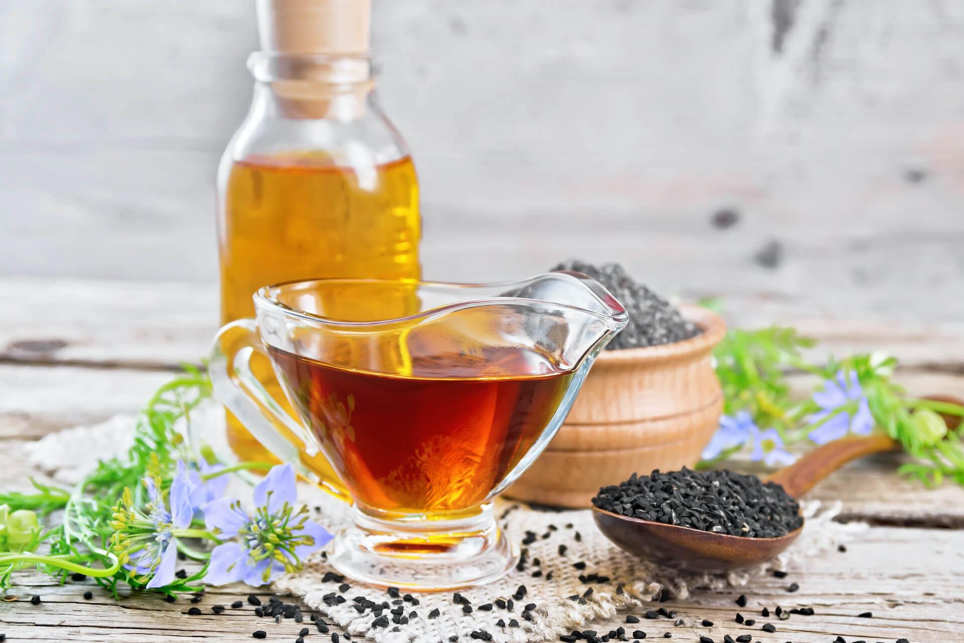 Ulje crnog kima u staklenoj šalici i bočici te sjemenke crnog kima  drvenoj žlici i drvenoj posudi