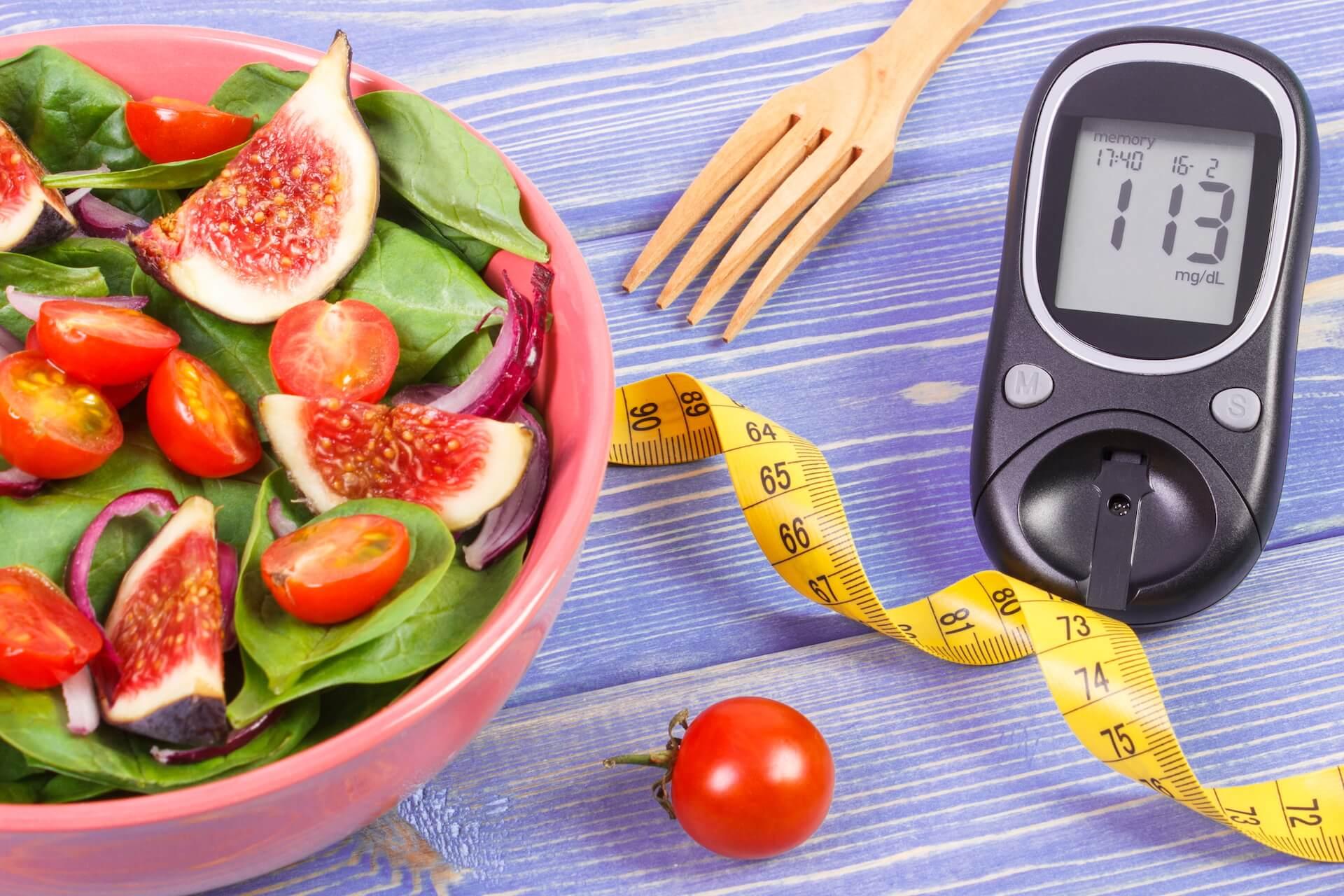 Salata u zdjeli, metar za mjerenje struka i glukometar