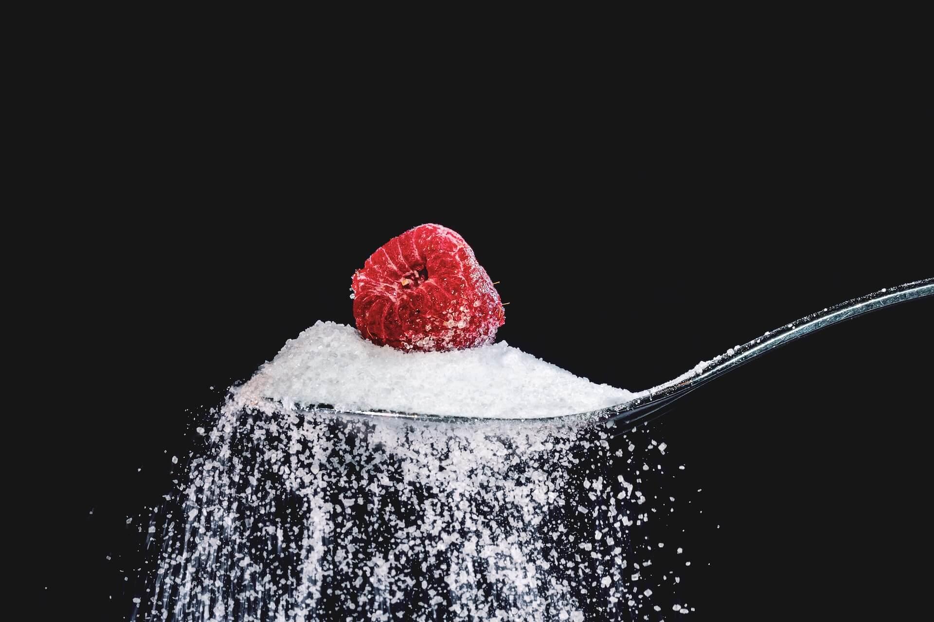 Bijeli šećer na žlici koji se lagano rasipava s malinom na vrhu
