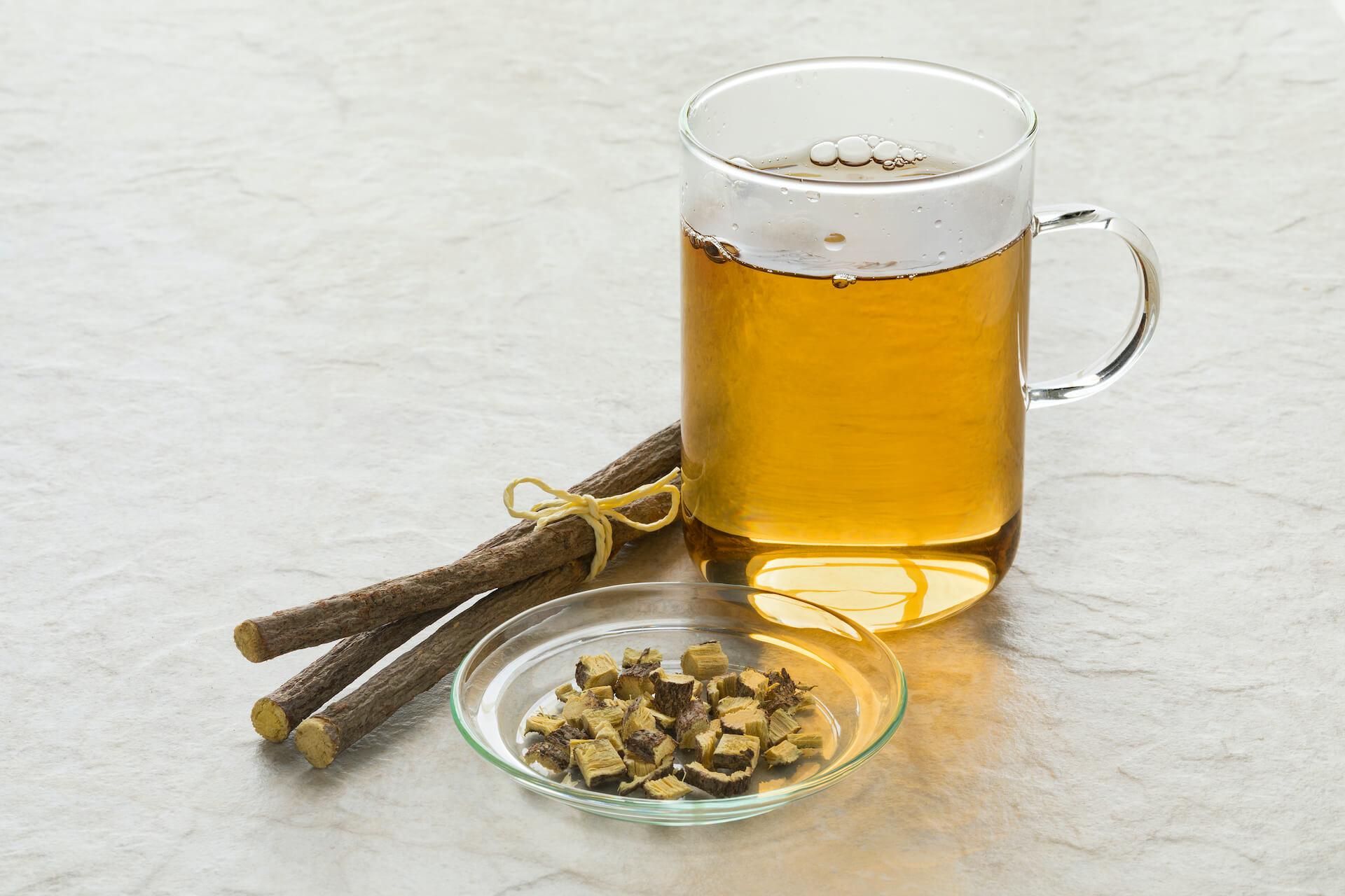 Sladić korijen i čaj od sladića u staklenoj šalici.