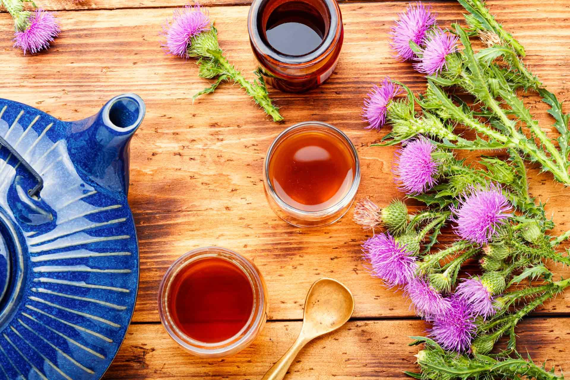 Čaj od čička u tri šalice, čajnik i svježi čičak sa strane