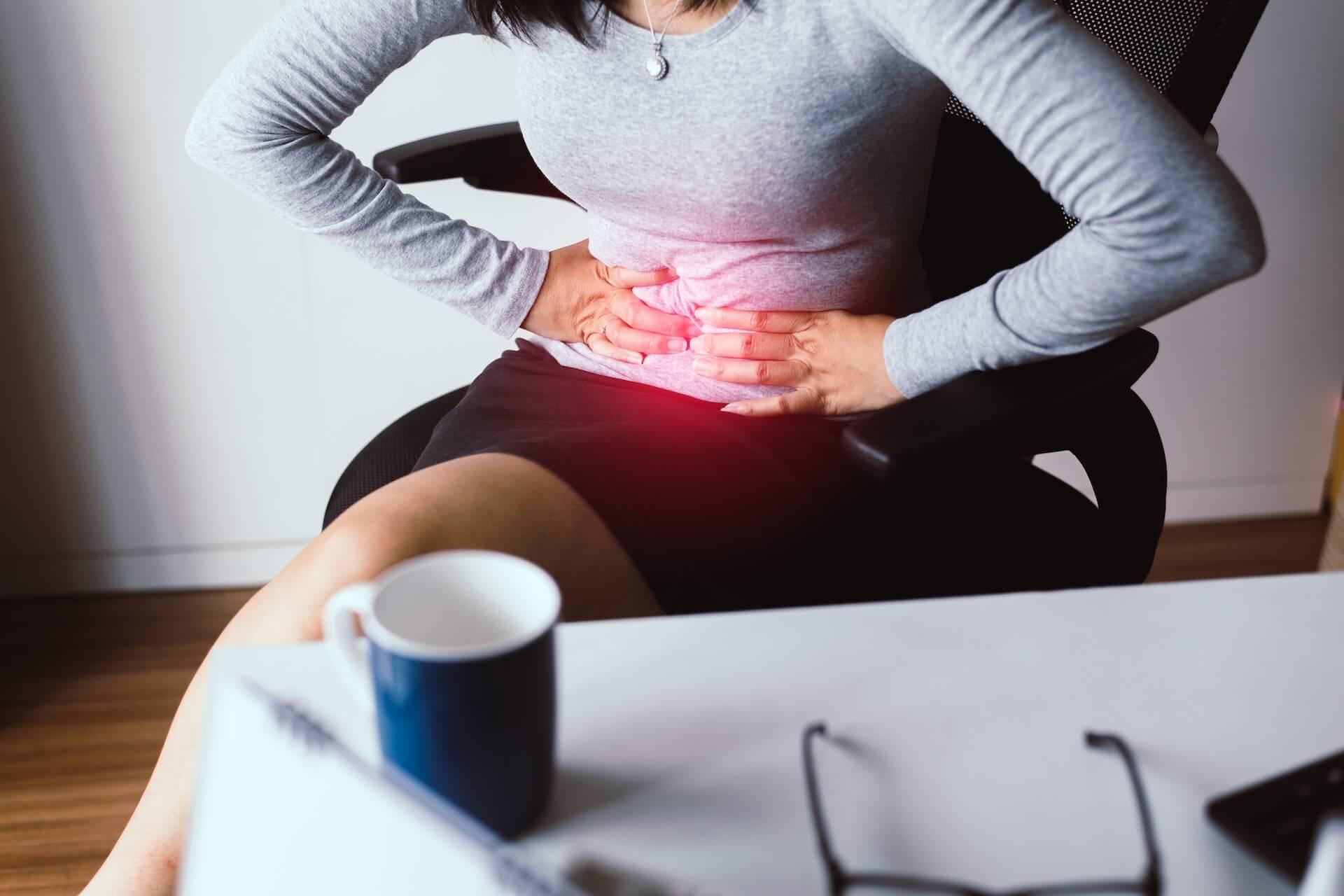 Žena u uredu se drži za bolan trbuh.
