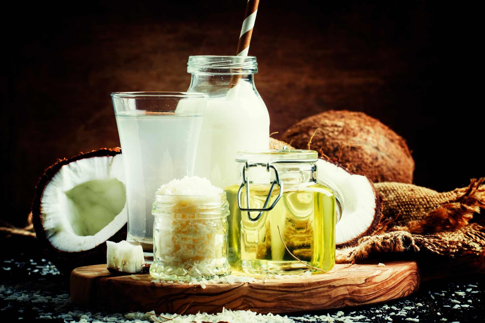 Kokosovo ulje, ribani kokos u staklenci, kokosova voda u čaši, kokosovo mlijeko sa slamkom i kokosovi orasi u pozadini