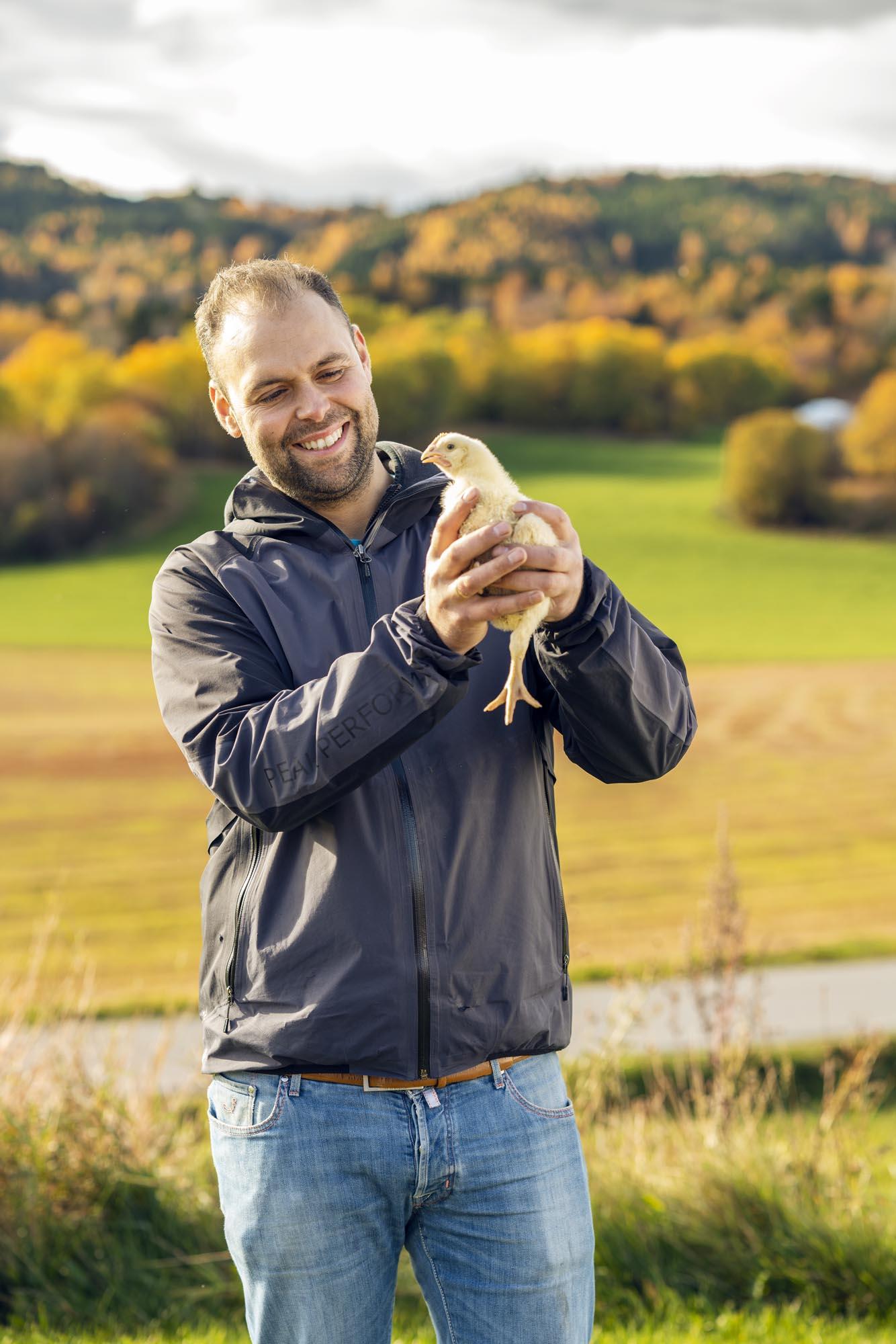 Mann som holder en kylling.
