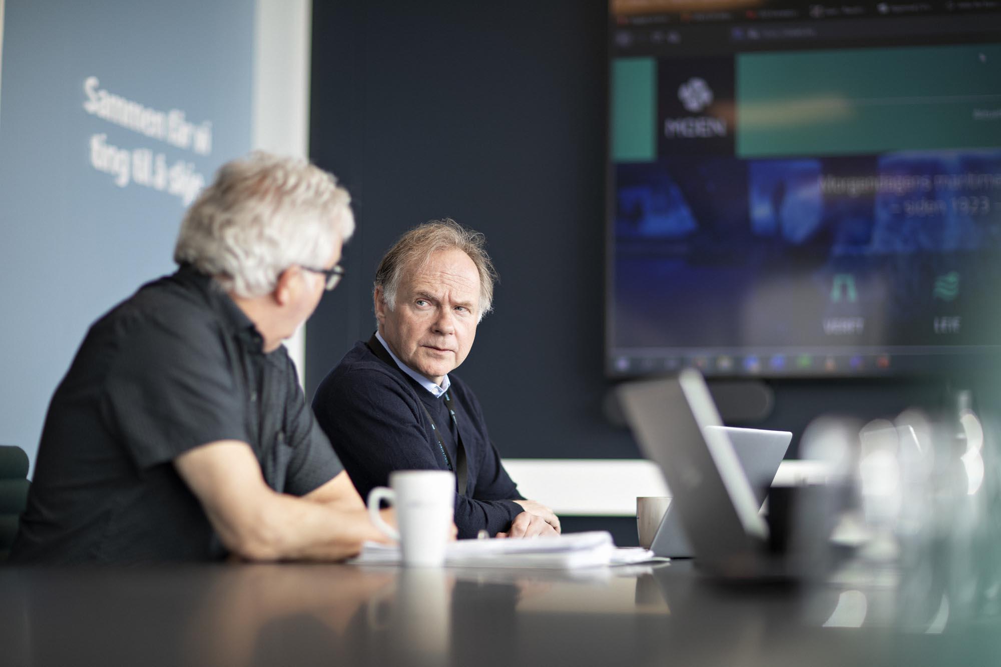 Mann som diskuterer noe i et møterom.