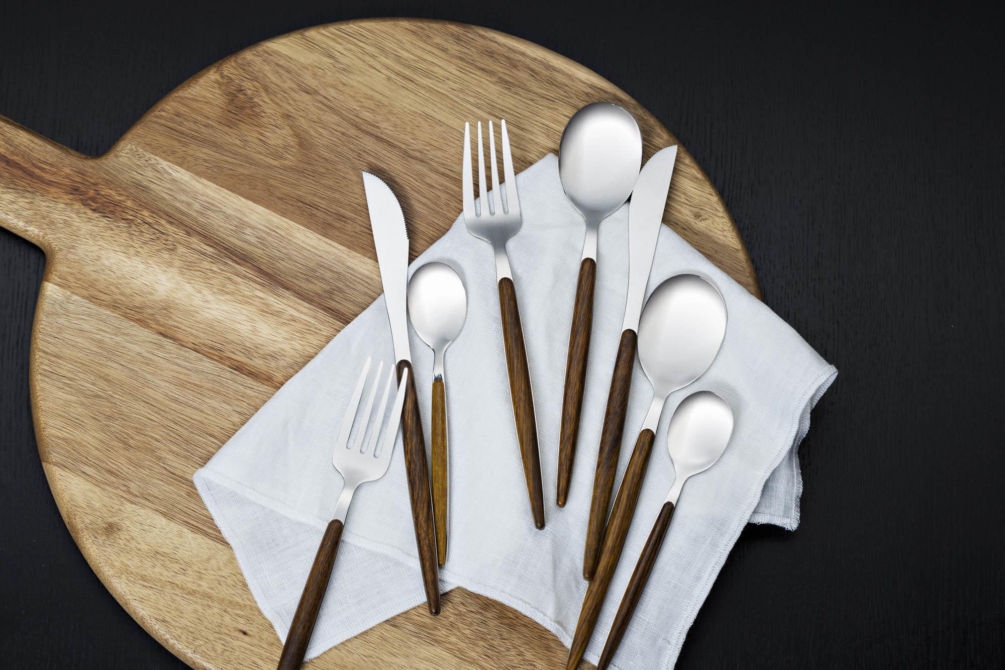 Miljøbilde av blankt bestikk med håndtak i treverk.