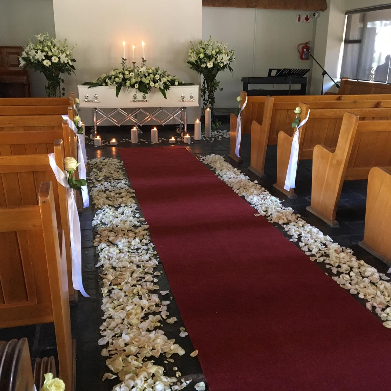A chapel setup for a funeral with petals along the floor