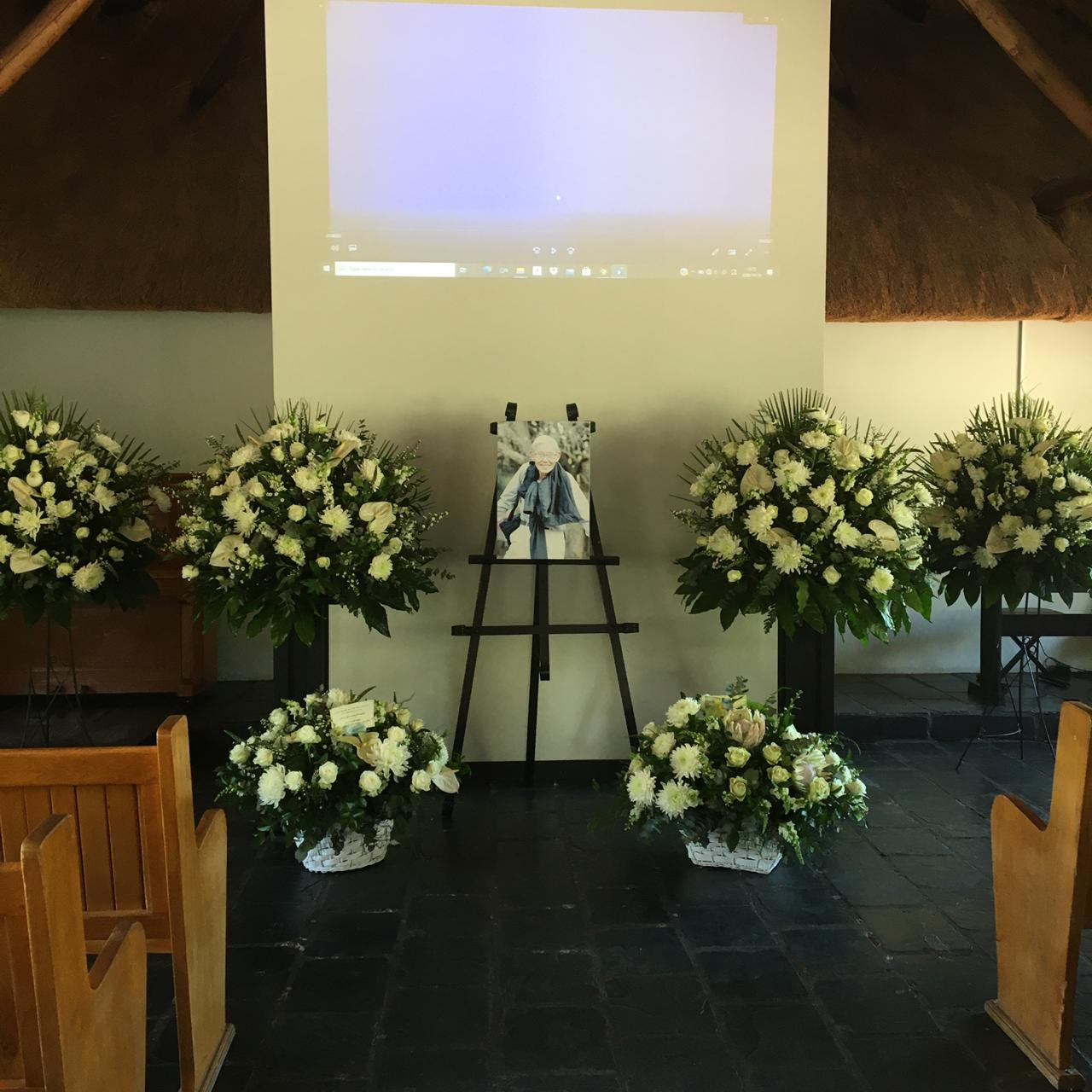 Chapel Setup including 2 baskets and 4 white flower arrangements