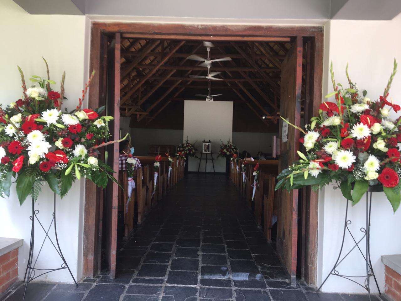 Chapel arrangement with pew decorations with red and white flowers. Please call for a quote.