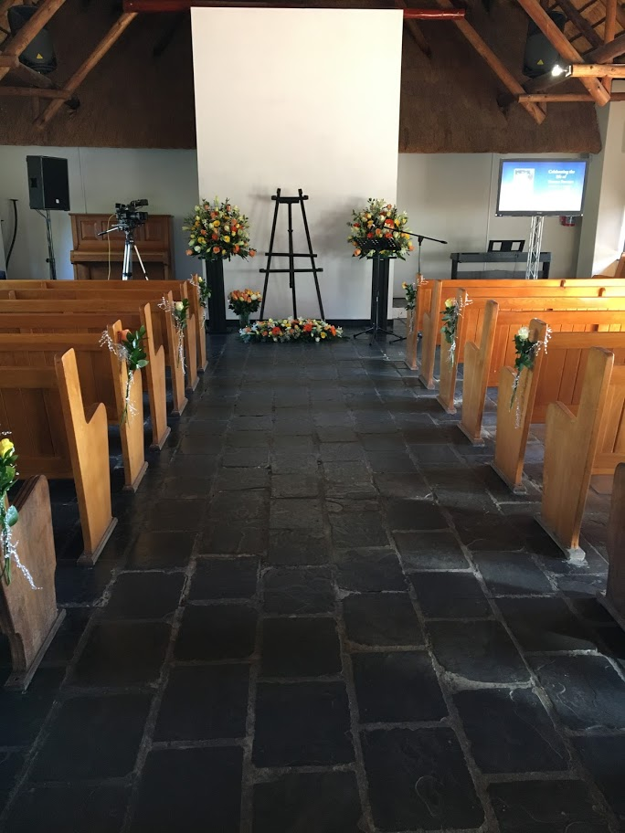 Chapel set up with church arrangements and pew decor