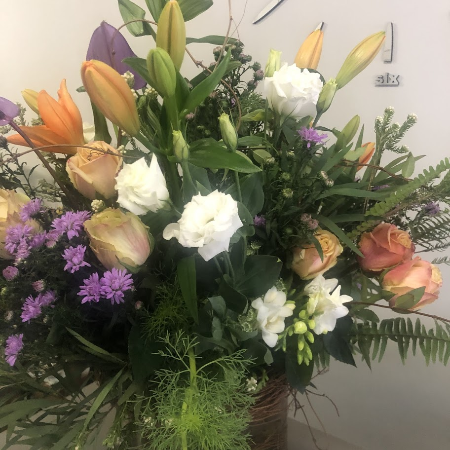 free styled vase filled with seasonl bright flowers