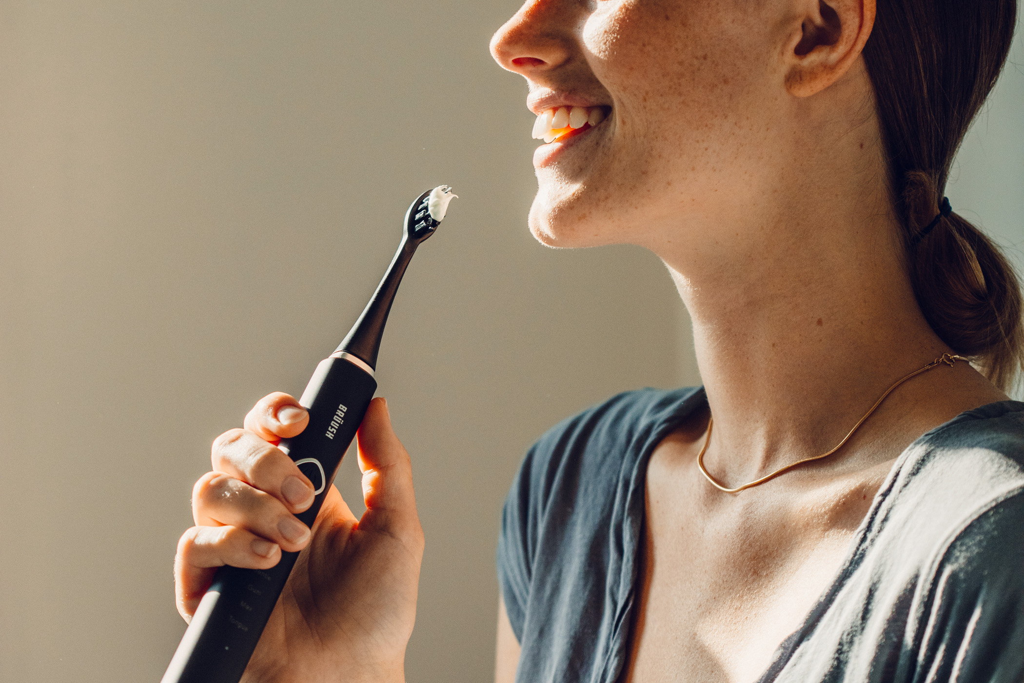 woman using best electric toothbrush