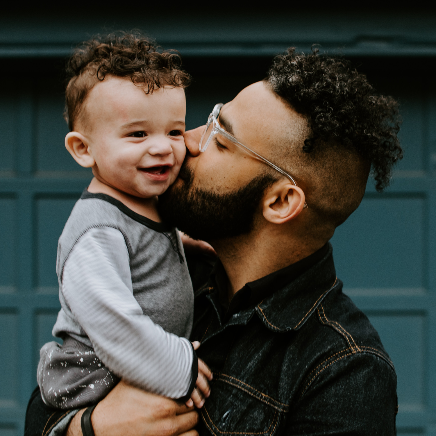 Black father holding baby and kissing him on the cheek.