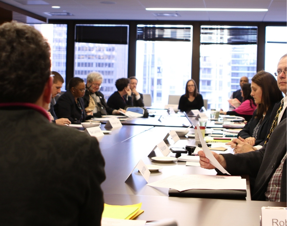A group of professionals sit around a conference table.
