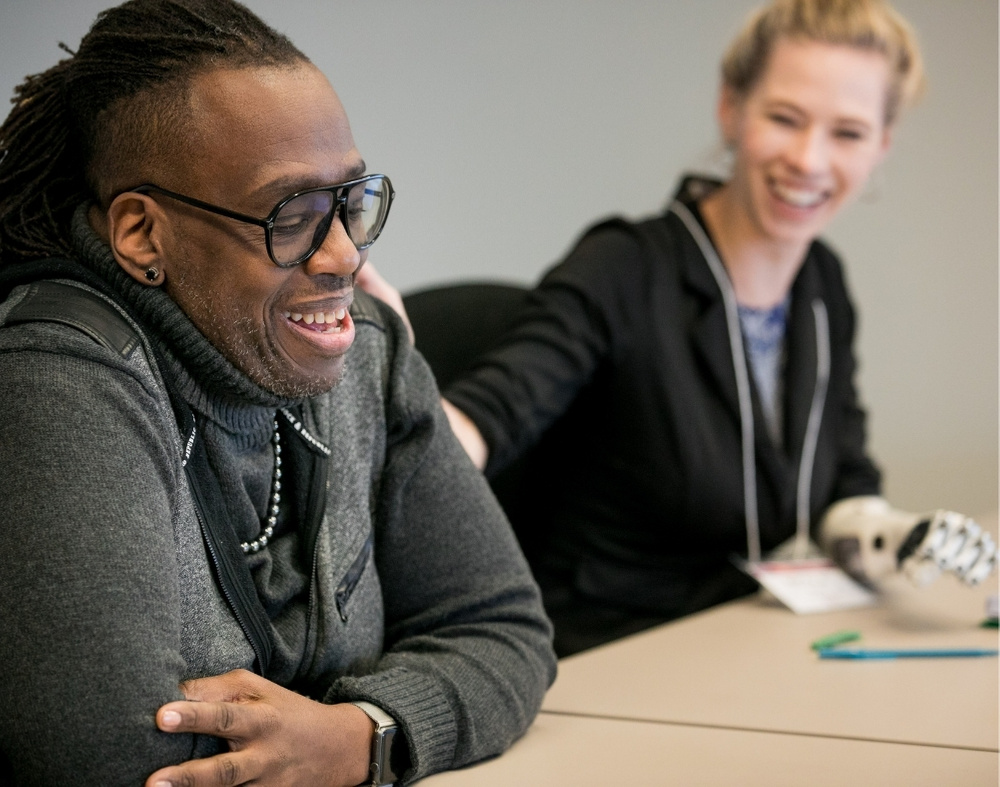 A black man in dreads and white blonde woman with her hair pulled back. Her hand is on his shoulder and they are laughing together.
