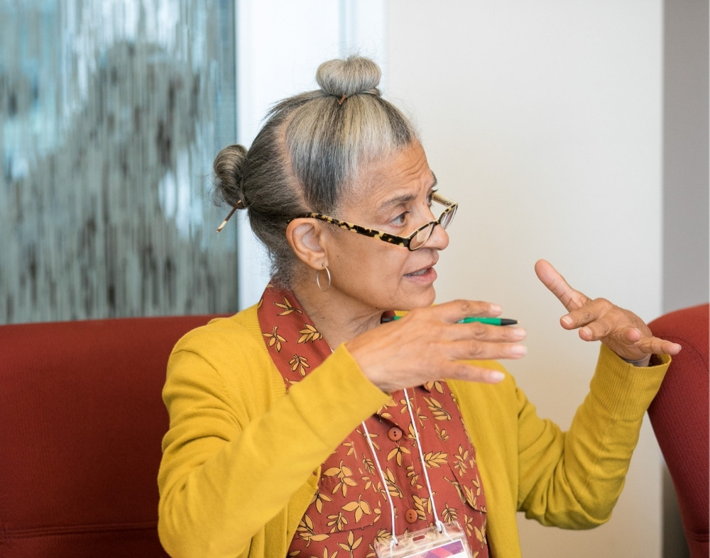A black senior citizen in a yellow cardigan with her gray hair up in fashionable buns explains something to someone off camera.