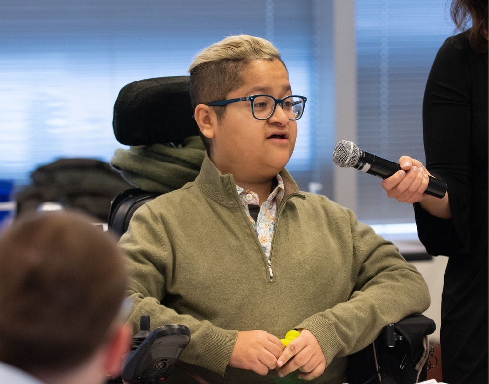 A LatinX man in glasses and a power chair speaks into a microphone. He has blonde hair pulled back into a ponytail and shaved sides.