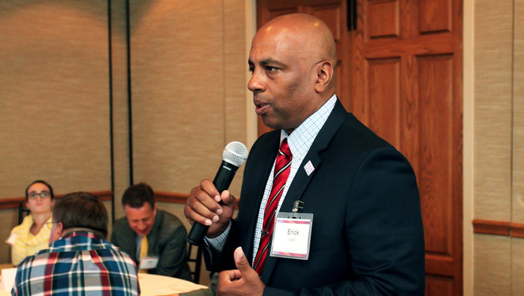 Erick Allen uses a microphone to address a room of people. He is a Black, bald man dressed in a dark suit with a red tie.
