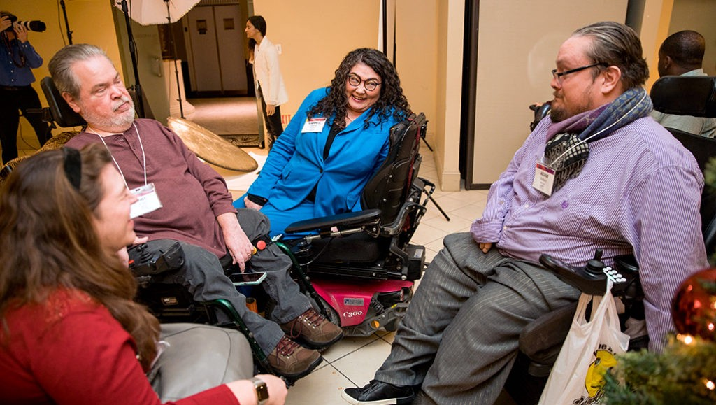 Rahnee Patrick engages in a casual group conversation with three adults. She has dark curly hair, medium-toned skin, glasses, uses a power chair, and is wearing a blue dress suit.