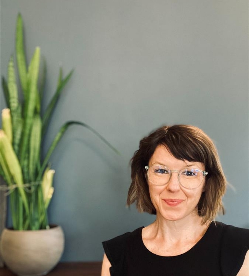 Robin has a short bob with wavy light brown hair and short side-swept bangs, light-tone skin, clear-framed glasses, and is wearing a black top.