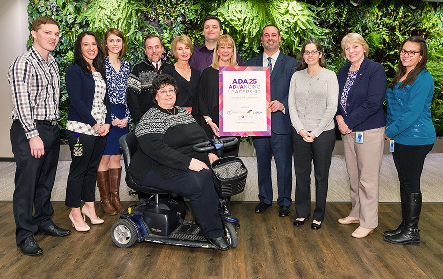 A group of 12 people of various identities pose with an ADA 25 Advancing Leadership sign.