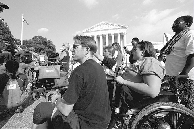 Karen Tamley observes a speaker in her power chair among a crowd on the White House lawn. She is a white woman with brown hair and uses a power chair.
