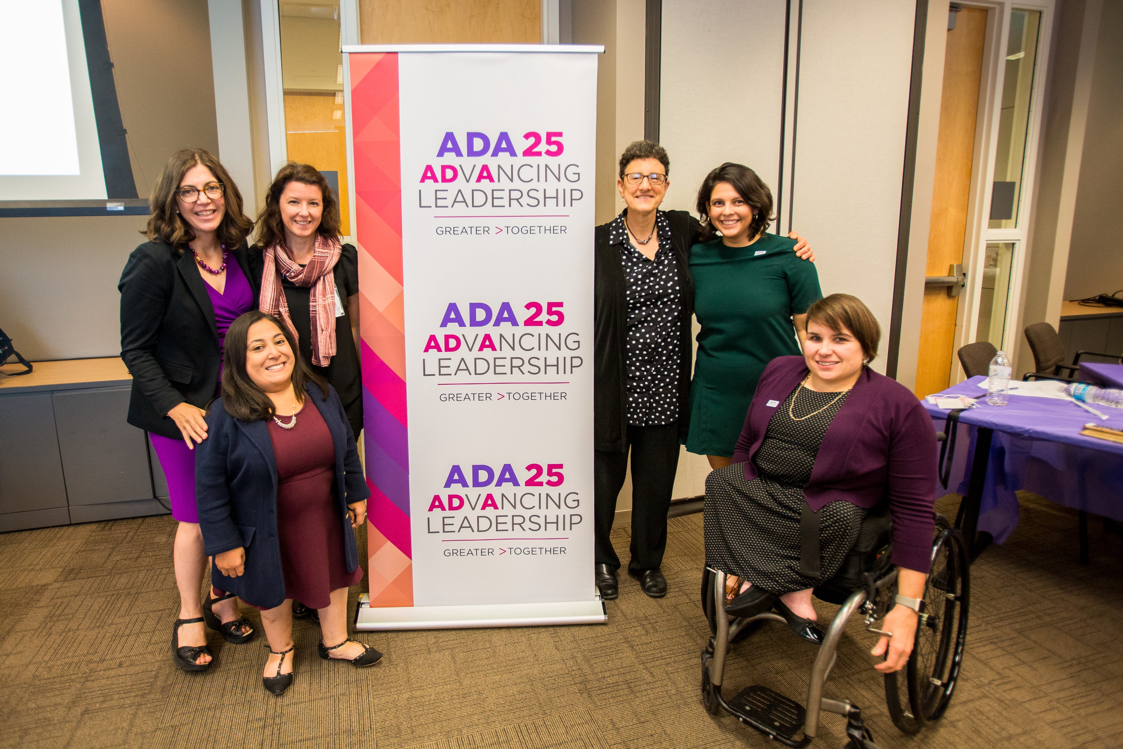 Disability Lead staff pose around an Advancing Leadership banner.