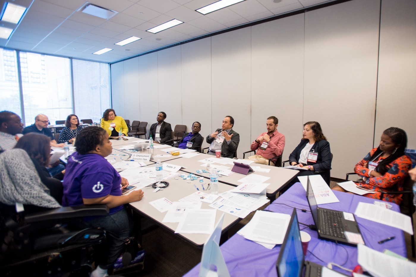 A group of people of various identities sit around a long conference table.