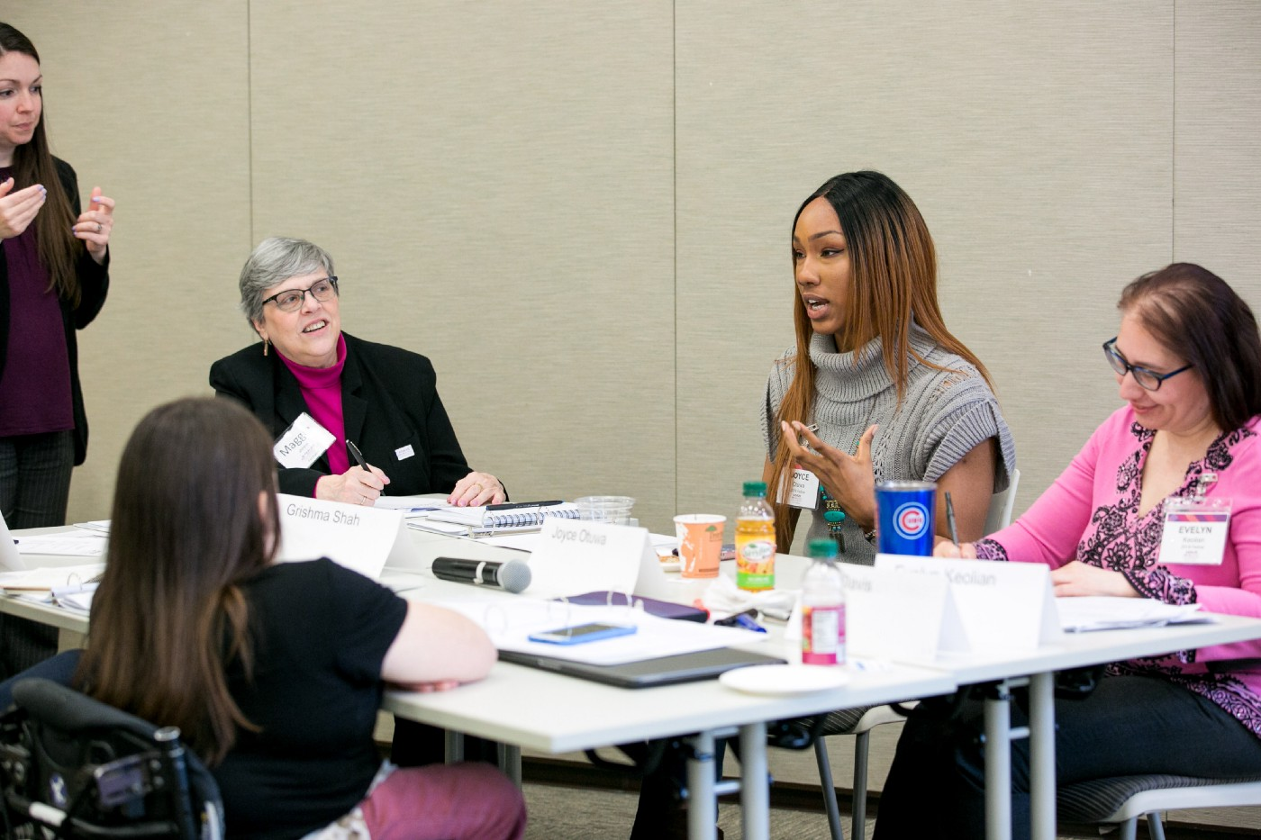 At a table, Joyce participates in a small group discussion. Her hair is long and brown, and she's wearing a gray turtleneck.