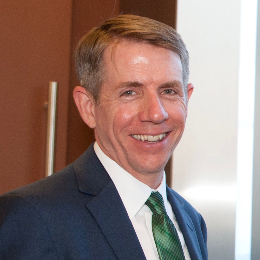 Kevin is smiling and posing in front of a wooden door. He has short gray hair, light-toned skin, and a navy suit with a blue and green argyle tie.